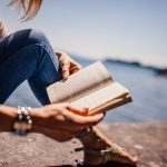 Woman sitting near the shore reading a book