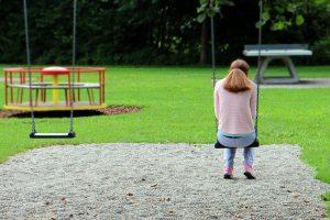 Girl sitting on swing alone