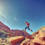 Man jumping while hiking among rock formations