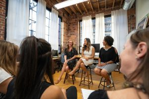 Three women are sitting in chairs leading a panel discussion in front of a group of women
