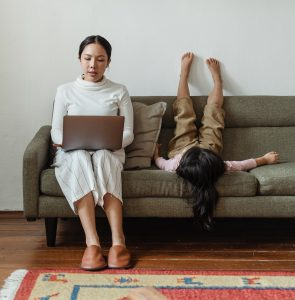 A woman is working on her computer, and her daughter is upside down on a couch
