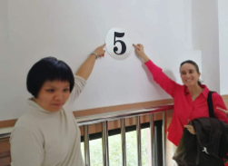 Zhan Ge and Helen pointing to a number five written on a wall.