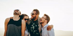 Four people are laughing and wearing sunglasses or glasses
