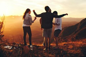 group of three to four people standing on hill at dusk, appear to be dancing